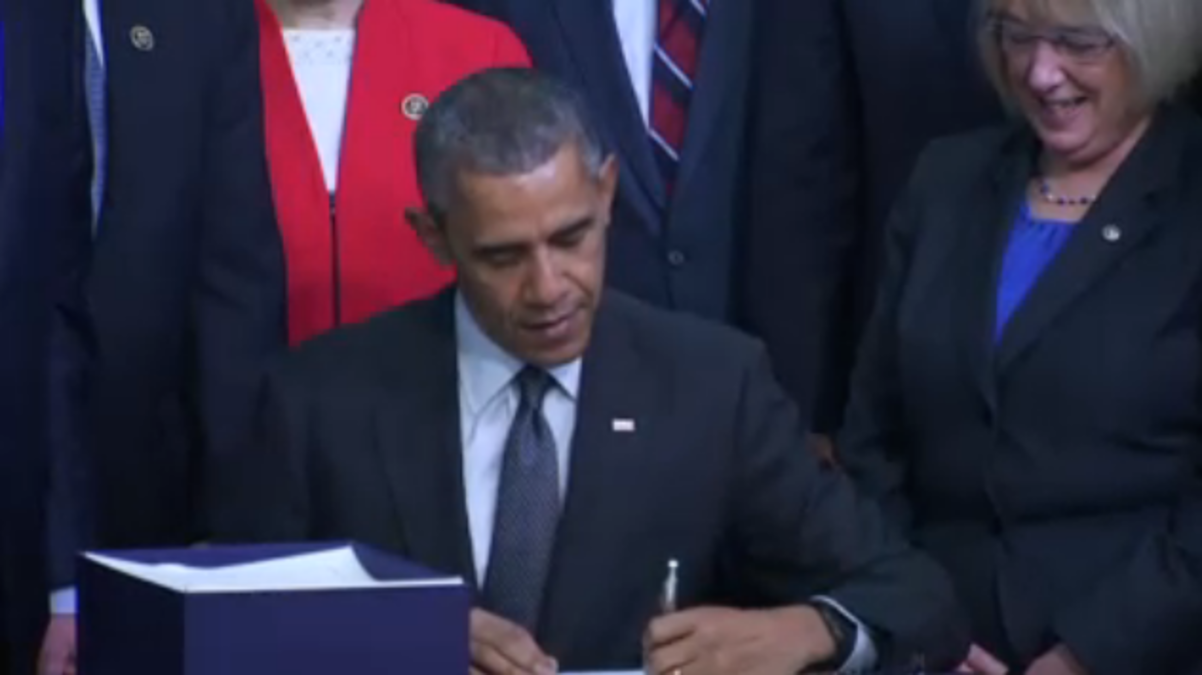 President Barack Obama signs the Every Student Succeeds Act into law with Senator Patty Murray at his side.
